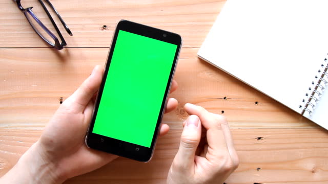 hand using mobile phone with green screen on wooden office table - top view video
