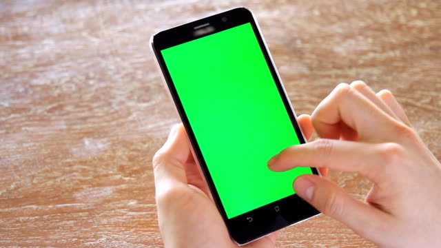 hand using mobile phone with green screen on wooden office table video