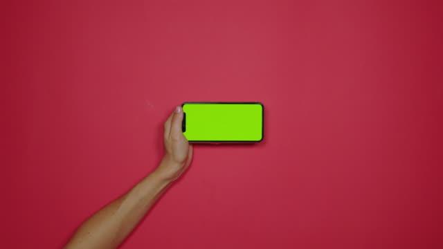 hand mit telefon mit green-screen über rote flach zu legen - blickwinkel der aufnahme stock-videos und b-roll-filmmaterial