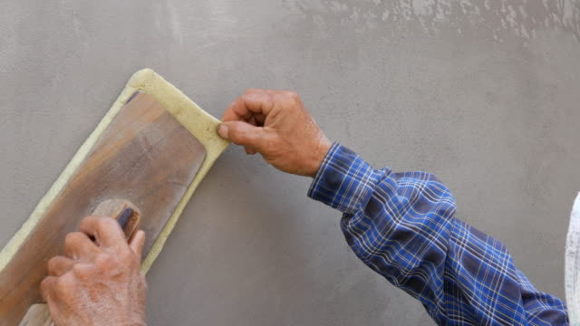 hand using trowel to finish wet concrete wall at construction site video