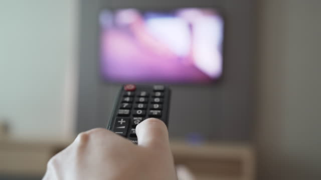 hand using tv remote control in the bedroom - bedroom video stock e b–roll