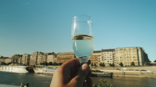A hand with a glass of champagne clinks. A party on the ship, a river cruise on the Danube. POV video To clink glasses on a pleasure ship. A party in a river cruise, a beautiful light before sunset winetasting stock videos & royalty-free footage