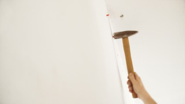 A hand with a hammer hammers a plastic dowel pin into the wall. Installation of a stretch ceiling. chandelier, floor lamp,