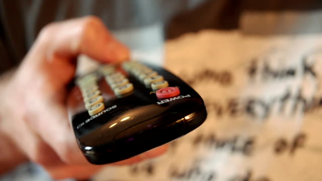 Hand with a television remote control changing channels. Front view Hand with a television remote control changing channels. Front view cable tv stock videos & royalty-free footage