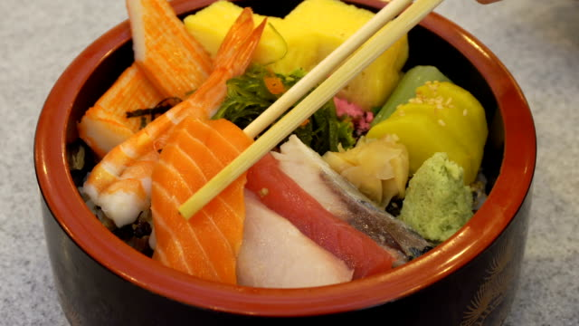 Hand with chopsticks fresh uncooked fresh salmon and egg with wasabi and vegetable in In japanese traditional bowl on wood table by motion. video
