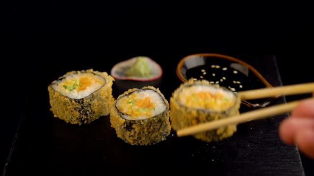 Hand with chopsticks taking roll sushi from dark plate video