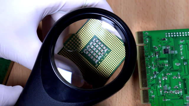 hand with magnifying glass examining computer cpu processor video