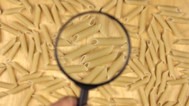 Hand with magnifying glass increases macaroni Hand with magnifying glass increases macaroni, top view uncooked pasta stock videos & royalty-free footage