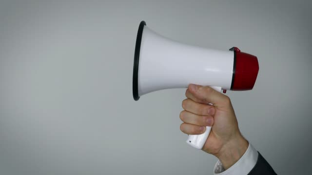 vídeos de stock e filmes b-roll de hand with megaphone on gray background with copy space - megafone