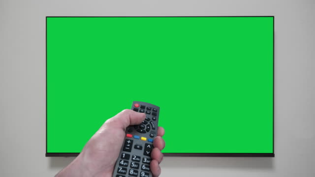 4k - hand with remote control changes channels tv. green screen. chroma key - television industry stock videos & royalty-free footage