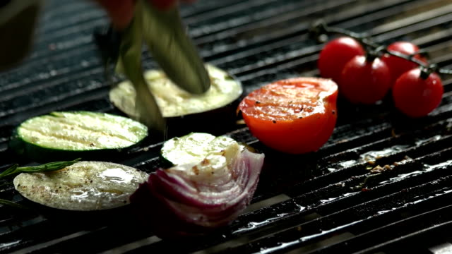 Hand with tongs grilling food. video