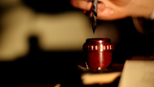 hand writes a letter with an old pen and inkwell