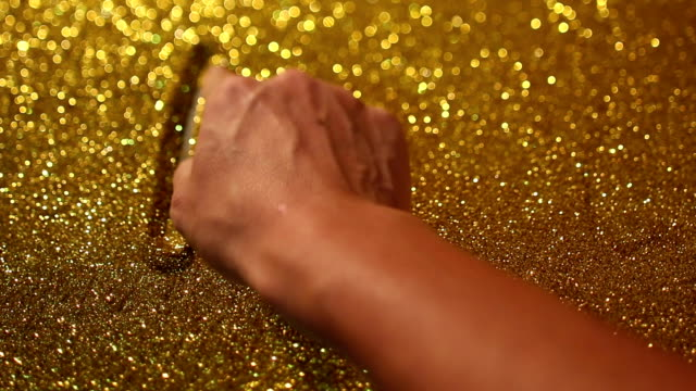 hand writing on golden sand background with word biz
