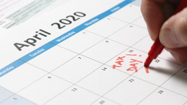Hand writing tax day on calendar
