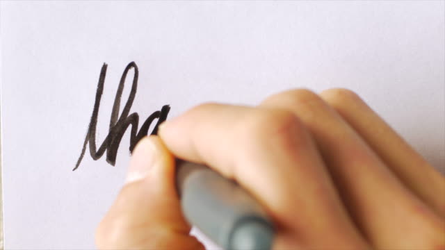 Hand writing the words THANK YOU and underlining them in cursive
