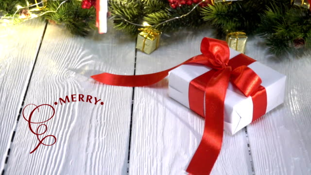 hand writing white merry christmas animation calligraphy lettering text on white wooden background with gifts and holidays decoration. 3d for video greeting card. happy feeling - pojedyncze słowo filmów i materiałów b-roll