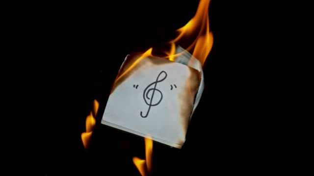 SLO MO LD Hand written treble clef symbol burning on a piece of paper