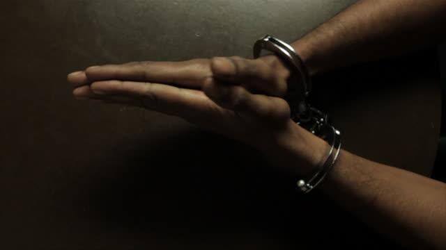 Handcuffed hands of a young black man. With your hands together. Prisoner. Manos esposadas de un hombre joven de raza negra. Con las manos juntas suplicando video
