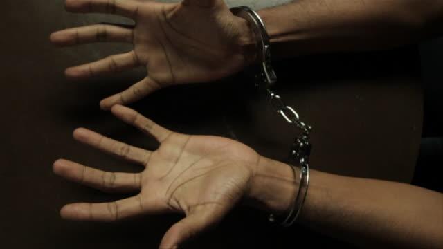 Handcuffed hands of a young black man. With your hands together. Prisoner. Manos esposadas de un hombre joven de raza negra. video