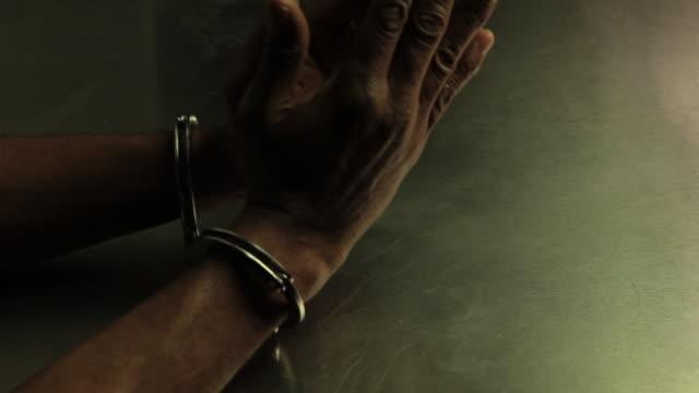 Handcuffed hands of an old African American man.  Manos esposadas de un hombre viejo de raza negra. video