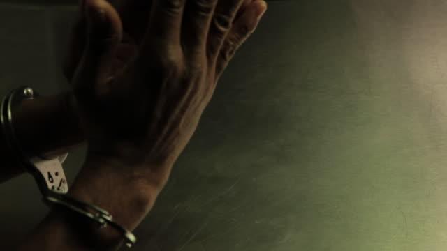 Handcuffed hands of an old man of black race.  Manos esposadas de un hombre viejo de raza negra. video