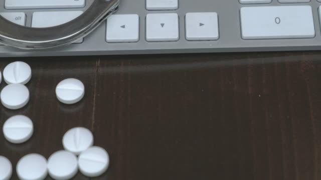 handfängsel och piller över datorns tangentbord. pan - amfetamin pills bildbanksvideor och videomaterial från bakom kulisserna