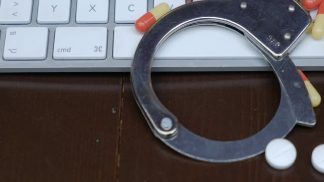 handcuffs and pills over computer keyboard. pan - censura video stock e b–roll