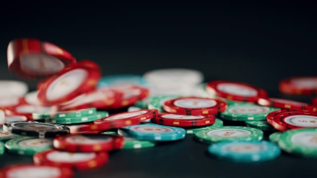 A handful of red poker chips are tossed into the pot in slow motion.