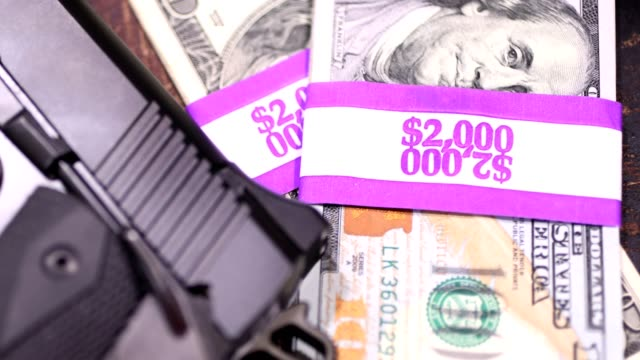 9mm handgun and stacks of $100 bills in $2000 wrappers. - cartello economico video stock e b–roll