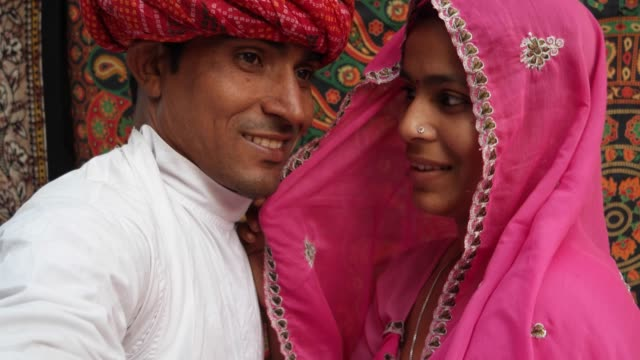Handheld POV of a camera taking selfie photos of a beautiful Indian couple in traditional clothing in Rajasthan, India