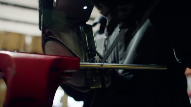 ein handheld bandsäge durchschneidet stahlrohr held in einem schraubstock - bandsäge stock-videos und b-roll-filmmaterial