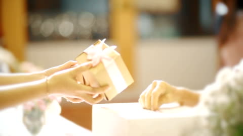 vidéos et rushes de appareil-photo à main de ms: belle boîte de cadeau étant donnée des mains aux mains sur la célébration de mariage. - cadeau