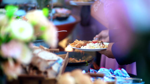 MS Hand-held Camera of People carrying a plate with meat dish on a buffet food table.