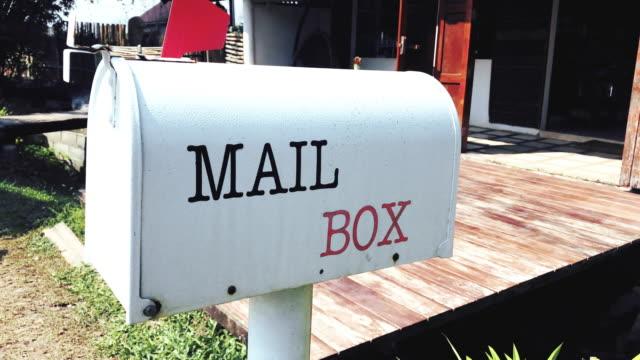 vídeos de stock, filmes e b-roll de ms mão-realizada câmera de u.s. caixa de correio branco na frente de uma casa. - correio correspondência