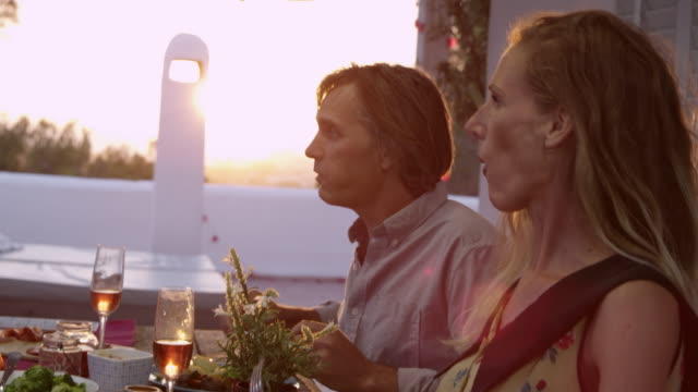 Handheld close up of two couples eating dinner on a terrace, shot on R3D video