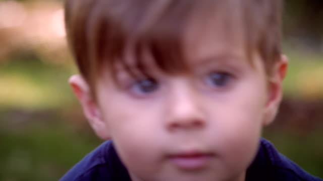 ハンドヘルドのクローズアップのポートレートと話している若い男の子にスロー mo ビデオ