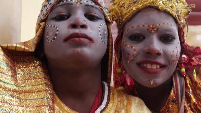 インドの町で 2 人の若い女の子のハンドヘルド クローズ アップ施しやお祝いの神性の女神に扮したし、観光客を見てカメラと笑顔を祝福 - 舞台化粧点の映像素材/bロール