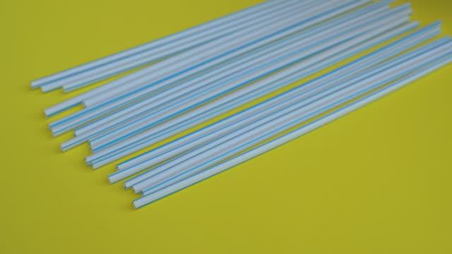 vidéos et rushes de plan rapproché portatif de beaucoup de pailles potables en plastique sur un fond jaune coloré - une main d'une personne a mis une paille potable de bambou au-dessus des plastiques. concept alternatif respectueux de l'environnement. lutte pour l'avenir sa - vaisselle picto