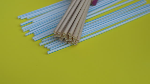 handheld closeup shot of lots of plastic drinking straws on a colourfull yellow background - a hand of a person put a bunch of paper drinking straws over the plastic ones. eco-friendly alternative concept. fight for the future without plastic - paglia video stock e b–roll