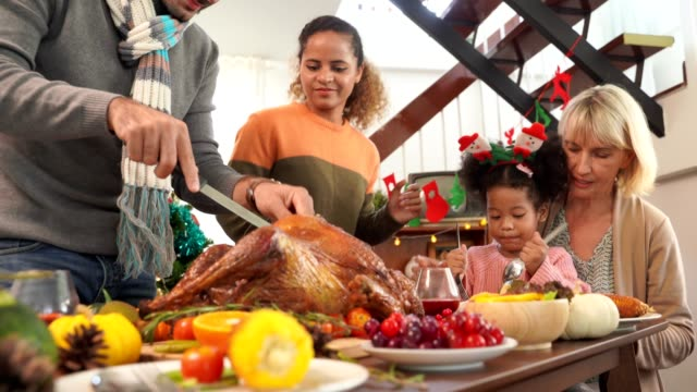 vídeos y material grabado en eventos de stock de padre de mano cortar pavo servido para la familia en la cena de acción de gracias. concepto de tradición de la celebración de acción de gracias - thanksgiving turkey