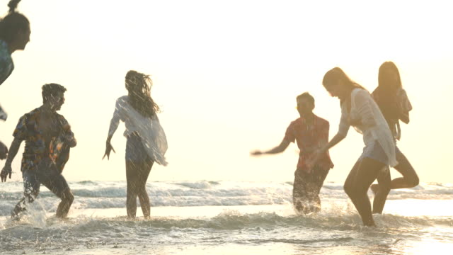 handheld low angle view: six cheerful friends with exciting beach activities under sunset handheld low angle view: six cheerful friends with exciting beach activities under sunset beach party stock videos & royalty-free footage