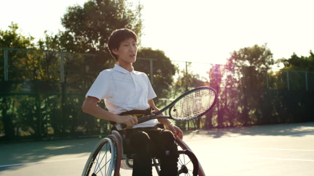 適応型テニス選手の練習のslo moハンドヘルドミッドショット - 車椅子スポーツ点の映像素材/bロール