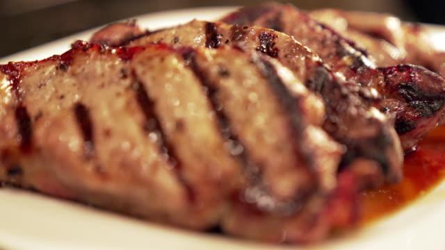 handheld moving slow motion close-up shot di ready to eat cotto, disossato, stagionato, succoso filetto di maiale braciole di maiale su un piatto - filetto video stock e b–roll