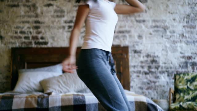 handheld of joyful african american teeanger girl have fun dancing near bed at home - pajamas stock videos & royalty-free footage