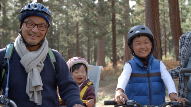 Handheld pan of Asian family on bikes in a forest, close up video