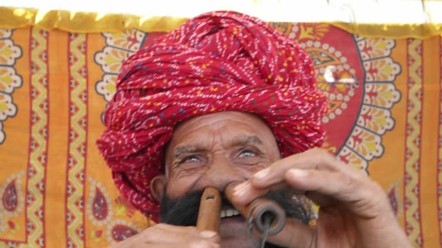 vídeos de stock e filmes b-roll de cu hand-held rajasthani elderly male starts to play the flute with his nose in front of a colourful fabric tent - hinduísmo