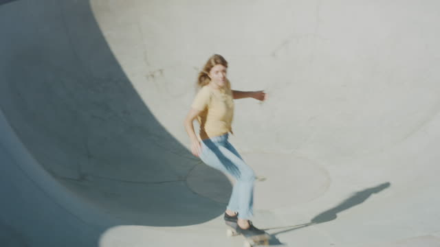 Handheld shot of a skater girl ripping in the pool bowl