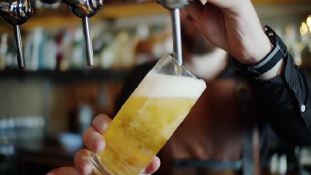 라거의 하프 파인트를 쏟아 붓는 바텐더의 핸드헬드 샷 - beer 스톡 비디오 및 b-롤 화면