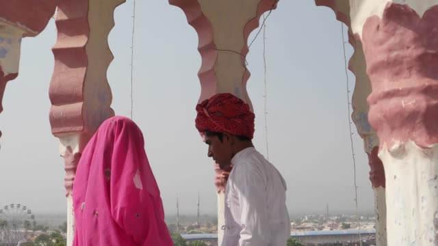 Handheld shot of beautiful Indian couple walking upto a view point in Pushkar, Rajasthan, India Beautiful young Indian couple in the religious Hindu holy town with temple and mela festival in Pushkar, Rajasthan with traditional architecture decoration, ornate and detailed indian culture stock videos & royalty-free footage