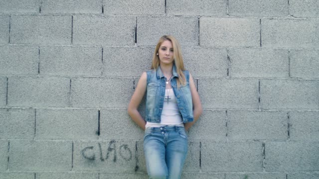 Handheld shot of blonde girl leaning on the wall video